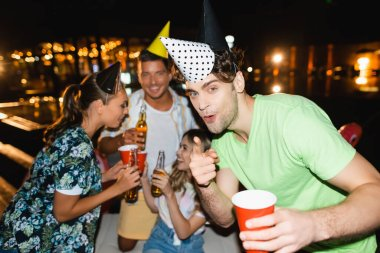 Selective focus of young man in party cap pointing with finger at camera near friends with beer outdoors at night stock vector
