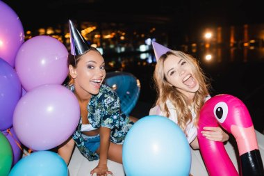 Selective focus of young women in party caps looking at camera near balloons at night stock vector