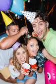 Selective focus of friends with disposable cups looking at camera near balloons outdoors at night