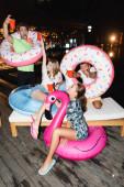 Mladí přátelé s plaveckými kroužky drží jednorázové poháry během večírku v noci