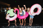 Young people dancing with swim rings near swimming pool at night