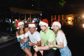 Přátelé v Santa klobouky drží sklenice a láhev šampaňského v blízkosti bazénu v noci