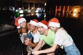 Přátelé v Santa klobouky otevření láhev šampaňského při oslavě nového roku v blízkosti bazénu v noci