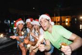 Selektive Fokussierung des Mannes mit Weihnachtsmannhut mit einem Glas Champagner und Wunderkerze in der Nähe von Freunden und nächtlichem Swimmingpool