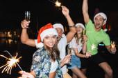 Selektiver Fokus einer jungen Frau mit Weihnachtsmannhut, die nachts ein Glas Champagner und Wunderkerzen in der Hand hält