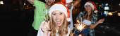 Horizontální obraz vzrušené ženy držící sklenici šampaňského a jiskry při oslavě nového roku v noci venku