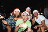 A fiatal barátok szelektív fókusza a kamerába néz az új év ünneplése alatt csillagszórókkal és pezsgővel éjszaka