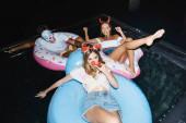 Szelektív fókusz a fiatalok party szarvak úszás gyűrűk a medencében éjszaka