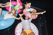 Blick aus dem Hochwinkel auf junge Leute in Party-Stirnbändern mit Blasenkitzlern, die nachts auf Ringen im Pool schwimmen