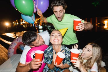 Selective focus of excited friends holding disposable cups and balloons near woman in party caps at night stock vector