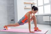 Sportlerin macht Ausfallschritt auf Fitnessmatte zu Hause