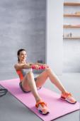 Sportovkyně s činkami dělá břišní svaly na fitness podložku doma