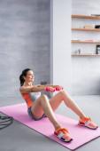 Mladá dospělá žena s činky dělá abs na fitness podložku doma