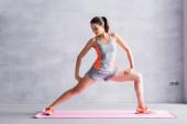 Sportswoman protahování na fitness podložka na šedém pozadí