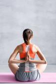 Fotografie Rückenansicht einer Frau mit betenden Händen, die auf einer Fitnessmatte sitzt