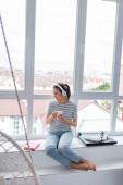 Selektiver Fokus der jungen Frau mit Kopfhörer in der Nähe von Buch und Plattenspieler auf der Fensterbank