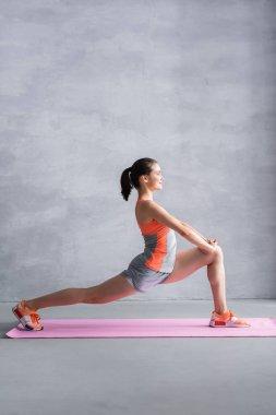 Sporcu kadının gri arka planda spor paspasına atlarken yan görünümü