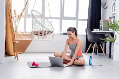 Sportswoman using laptop on fitness mat near bottle of water and dumbbells
