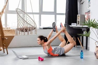 Side view of sportswoman working out near laptop on fitness mat near dumbbells and water