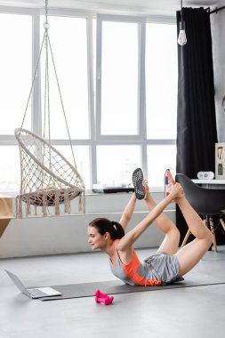 Sportswoman training near laptop and dumbbells on fitness mat in living room
