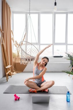 Young woman stretching while training on fitness mat near laptop, water and dumbbells at home