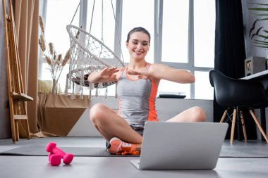 Young woman looking at laptop while training on fitness mat near dumbbells at home