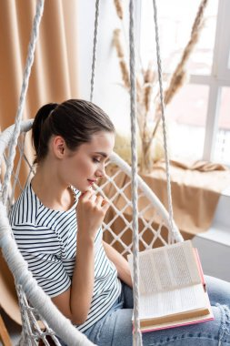 Selective focus of young woman reading book in hanging armchair at home