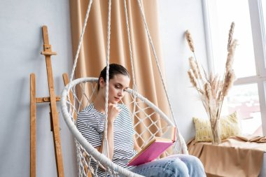 Young woman reading book while sitting in hanging armchair at home