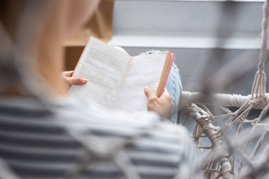 Selective focus of woman reading book in hanging armchair