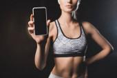 Oříznutý pohled na ženu ukazující mobil s prázdnou obrazovkou na černém pozadí