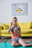 Frontansicht der Sportlerin auf Fitnessmatte in der Nähe der Sportflasche zu Hause