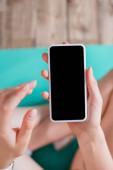 Selektivní zaměření ženy s mobilním telefonem s prázdnou obrazovkou