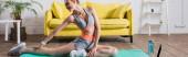 Panoramatický záběr sportovkyně trénink na fitness podložku v blízkosti sportovní láhve doma