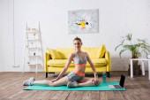 Sportswoman školení v blízkosti notebooku a sportovní láhev na fitness podložku doma