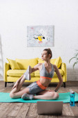 Sportswoman exercising near bottle of water and laptop on fitness mat at home