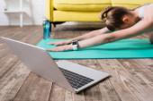Nahaufnahme von Laptop in der Nähe von Sportlerin Stretching auf Fitnessmatte zu Hause