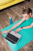 Lächelnde Sportlerin mit Laptop auf Fitnessmatte zu Hause