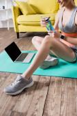 Vágott kilátás mosolygós sportos nő gazdaság sport palack közelében laptop otthon