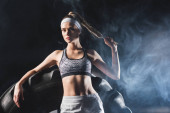 Selektivní zaměření sportovkyně dotýkající se vlasů v blízkosti pneumatiky ve sportovním centru s kouřem