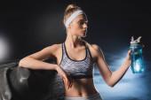 Selektivní zaměření sportovkyně držící sportovní láhev v blízkosti pneumatiky ve sportovním centru s kouřem