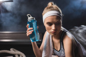 Photo Selective focus of young sportswoman with towel holding sports bottle in gym with smoke