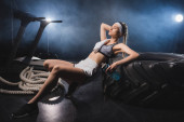 Sportswoman with towel and sports bottle looking away near tire and battle rope in gym with smoke