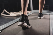 Fotografie Ausgeschnittene Ansicht einer Sportlerin, die auf Laufband im Sportzentrum läuft