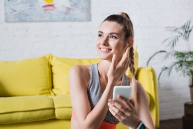 Sportswoman with cellphone looking away and touching wireless earphone at home