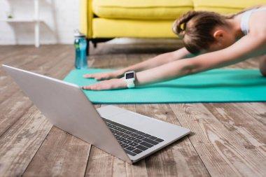 Spor kadının yakınındaki dizüstü bilgisayarın görüntüsü evde spor minderinin üzerinde geriniyor.
