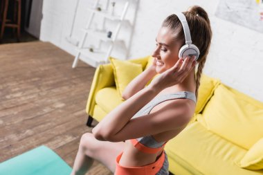 Positive sportswoman listening music in headphones while training at home
