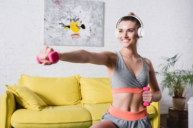 Selective focus of smiling sportswoman in headphones training with dumbbells in living room