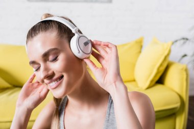 Smiling woman with closed eyes listening music in headphones at home stock vector