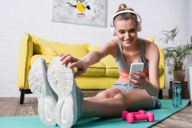 Selective focus of smiling sportswoman in headphones stretching and using smartphone at home