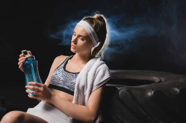 Selective focus of young sportswoman with towel looking at sports bottle near tire in gym with smoke stock vector
